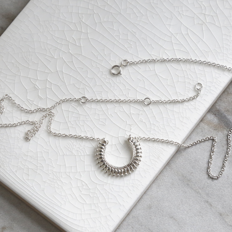 Sterling silver Marrakech horseshoe necklace on white background with sterling silver chain splayed out.