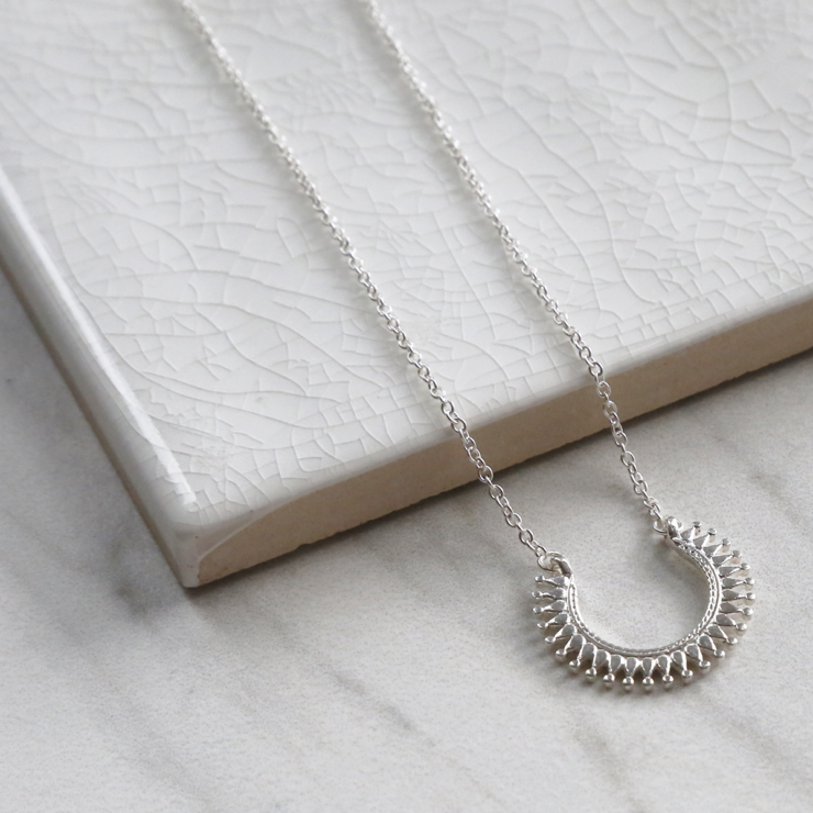 Sterling silver Marrakech horseshoe necklace on white background. Close up of intricate detail.