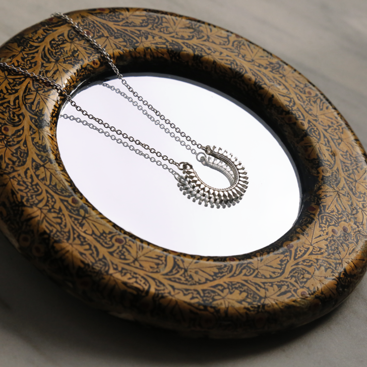 Sterling silver Marrakech horseshoe necklace on decorative mirror..