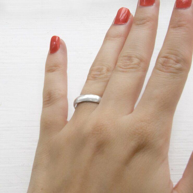 Polished sterling silver friendship ring on model's finger.