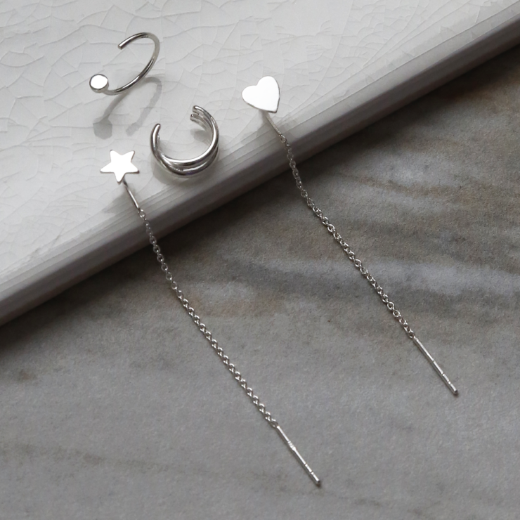 Sterling silver curated ear earring pack containing four earrings. On white background. Showing ear cuff on side angle.
