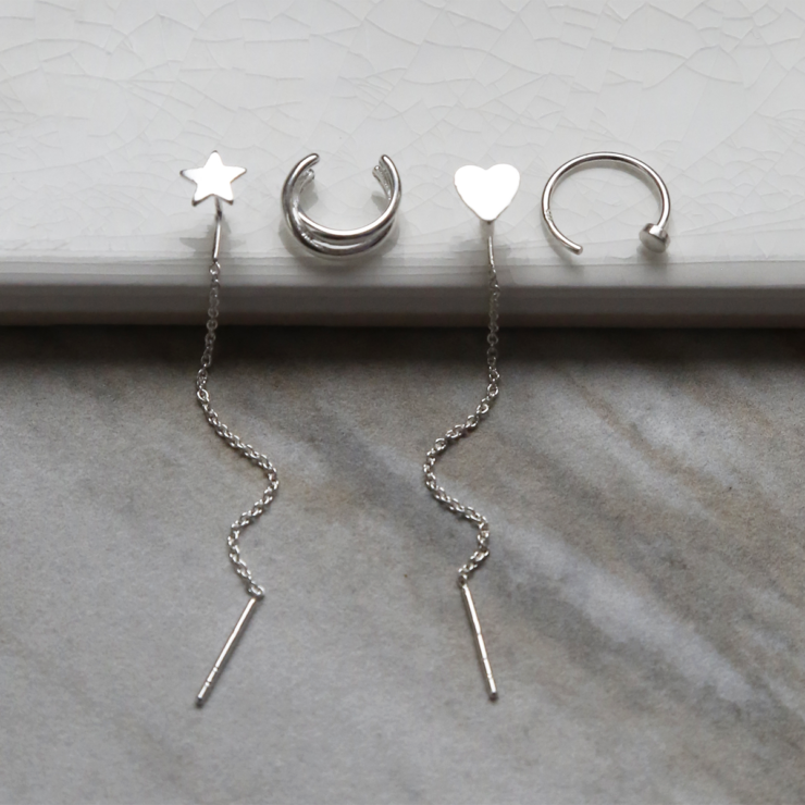 Sterling silver curated ear earring pack containing four earrings. On white background. Light shining on heart and star ear threaders.