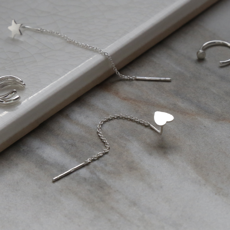 Sterling silver curated ear earring pack containing four earrings. On white background. Showing close up of heart ear threader.