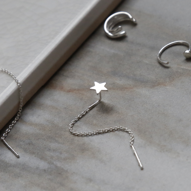 Sterling silver curated ear earring pack containing four earrings. On white background. Showing close up of star ear threader.