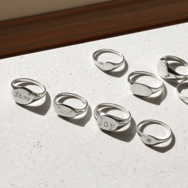 Engraved with shine sparkle joy and star round oval landscape and small sterling silver signet rings in sunlight