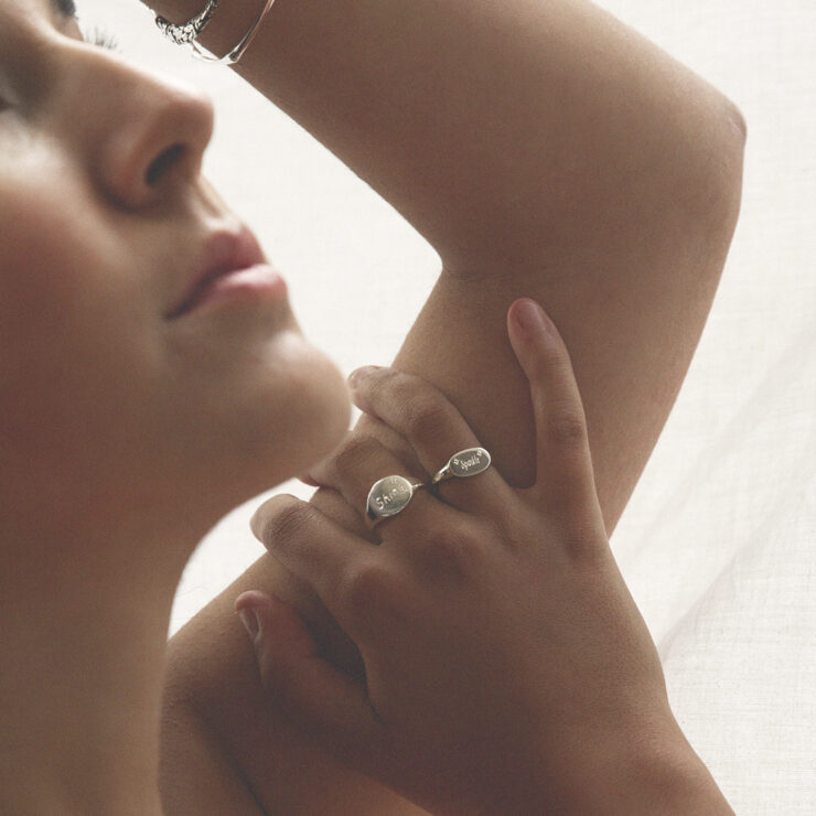 Model wearing two engraved with shine and sparkle oval and landscape sterling silver signet rings