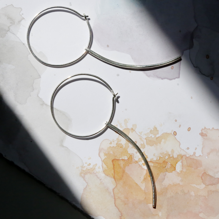 Silver Hoop Earrings with Claw on watercolour paper background and shadows