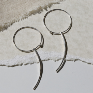 Silver Hoop Earrings with Claw on cream paper background
