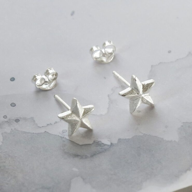 A pair of sterling silver solid star studs sat on a white marble background