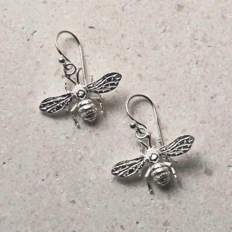 sterling silver dangly bee earrings laid out diagonally