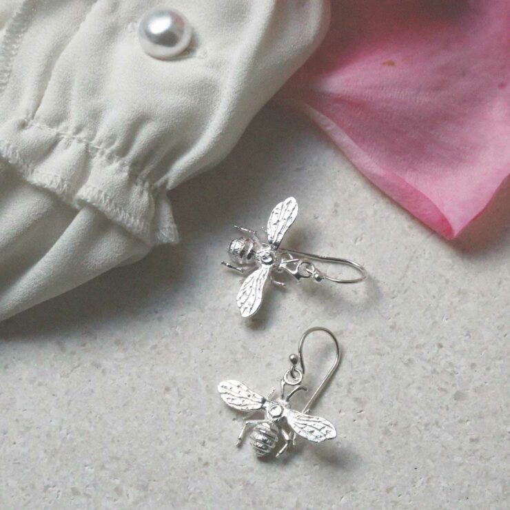 sterling silver dangly bee earrings laid out with fabric