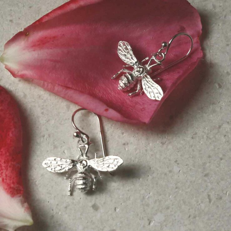 sterling silver dangly bee earrings laid out with petals