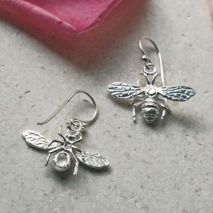 sterling silver dangly bee earrings laid out with petal