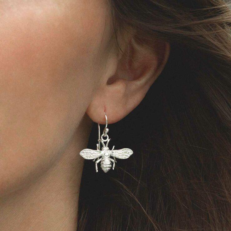 model wearing sterling silver dangly bee earrings