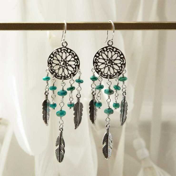 sterling silver dangly turquoise stone dream catcher earrings hung on rail