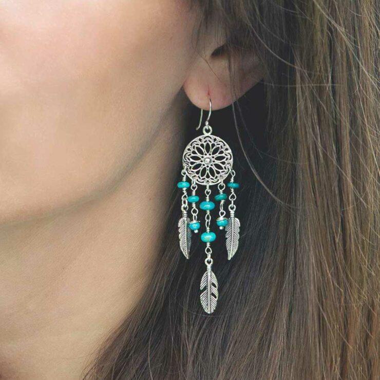 model wearing sterling silver dangly turquoise stone dream catcher earrings