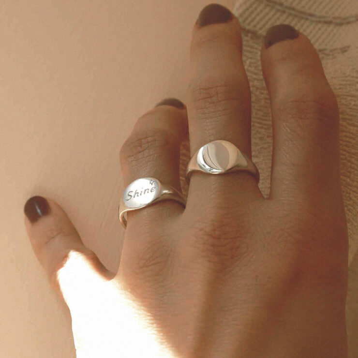 Hand wearing two engraved with shine oval sterling silver signet rings