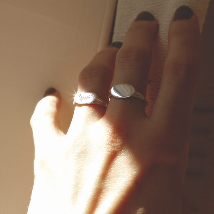 Hand wearing two engraved with sparkle wide landscape sterling silver signet rings