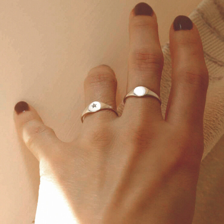 Hand wearing two engraved with star small sterling silver signet rings
