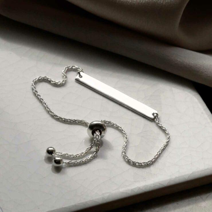 plain sterling silver adjustable identity bracelet laid out