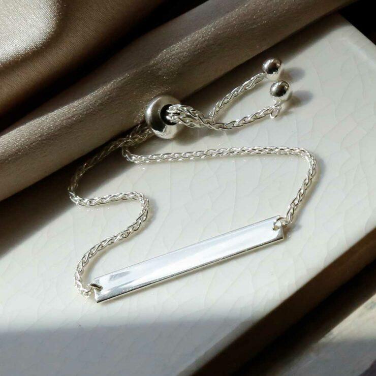 plain sterling silver adjustable identity bracelet laid out on tile