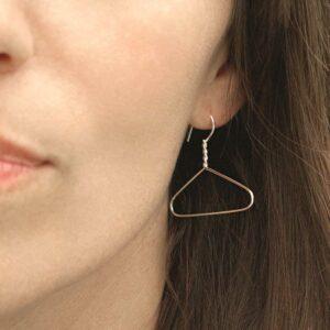 model wearing sterling silver coat hanger earrings