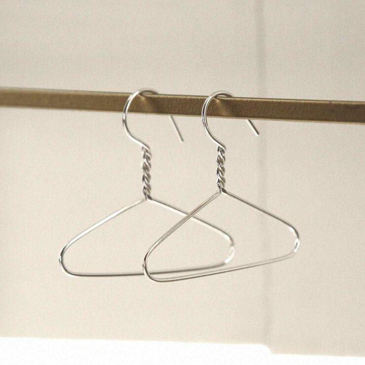 sterling silver coat hanger earrings hung on rail