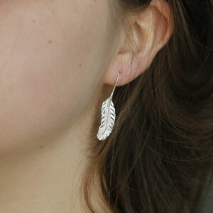 Sterling Silver Feather Drop Earrings Hanging from a ladies ear
