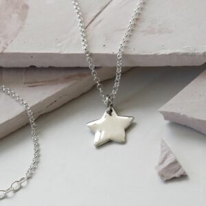 Sterling Silver Polished Star Necklace Hanging over slate with a chain