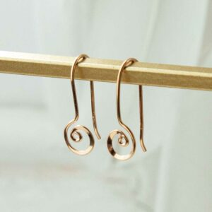 rose gold ear threaders on stand