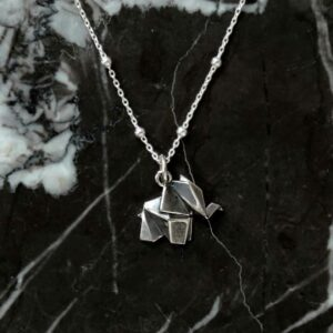 sterling silver origami elephant necklace on marble background