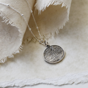 Sterling Silver Roman Head Coin Necklace hanging on linen