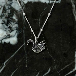 Sterling silver origami swan necklace on satellite chain on marble background