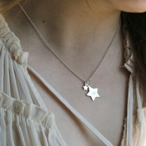 Sterling Silver Double Star Necklace hanging from a girls neck