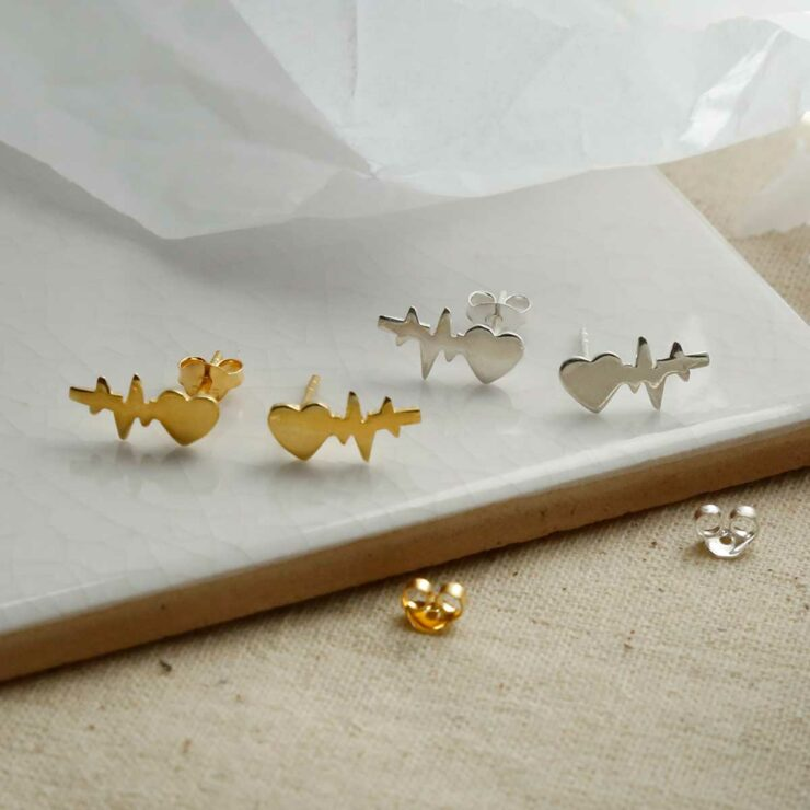 Gold Plated and Sterling Silver Heart Wave Studs sat on marble with shadows being cast