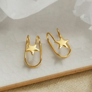 gold plated Sterling Silver Star Ear Cuffs sat on a marble tile with their shadow being cast
