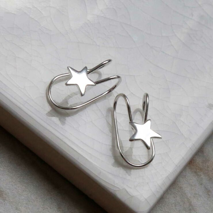 Sterling Silver Star Ear Cuffs sat on a marble tile with their shadow being cast
