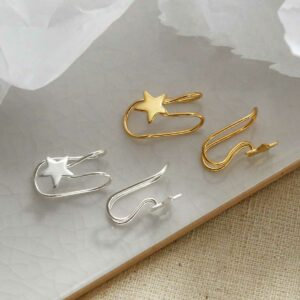 Sterling Silver and gold plated Star Ear Cuffs sat on a marble tile with their shadow being cast