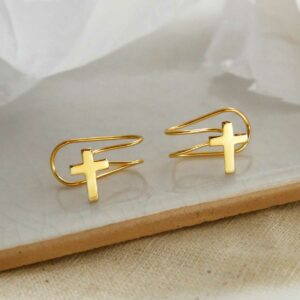 gold plated cross ear cuff on a marble slab