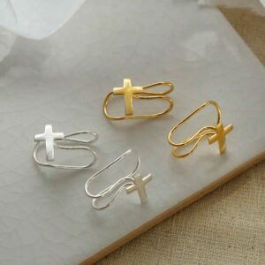 gold plated and Sterling silver cross ear cuff on a marble slab