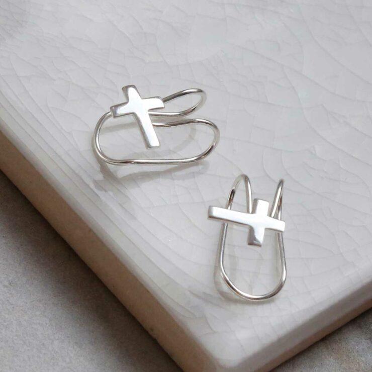 Sterling silver cross ear cuff on a marble slab