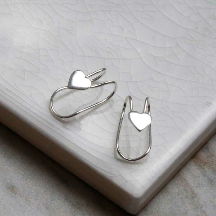 Sterling Silver Heart Ear Cuffs on a white marble tile