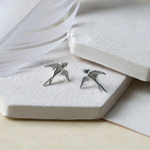 Swallow studs on cermaic tiles with white feather props
